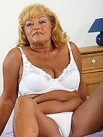 Bronzed grandma with big soft breasts spreads her shaved pussy